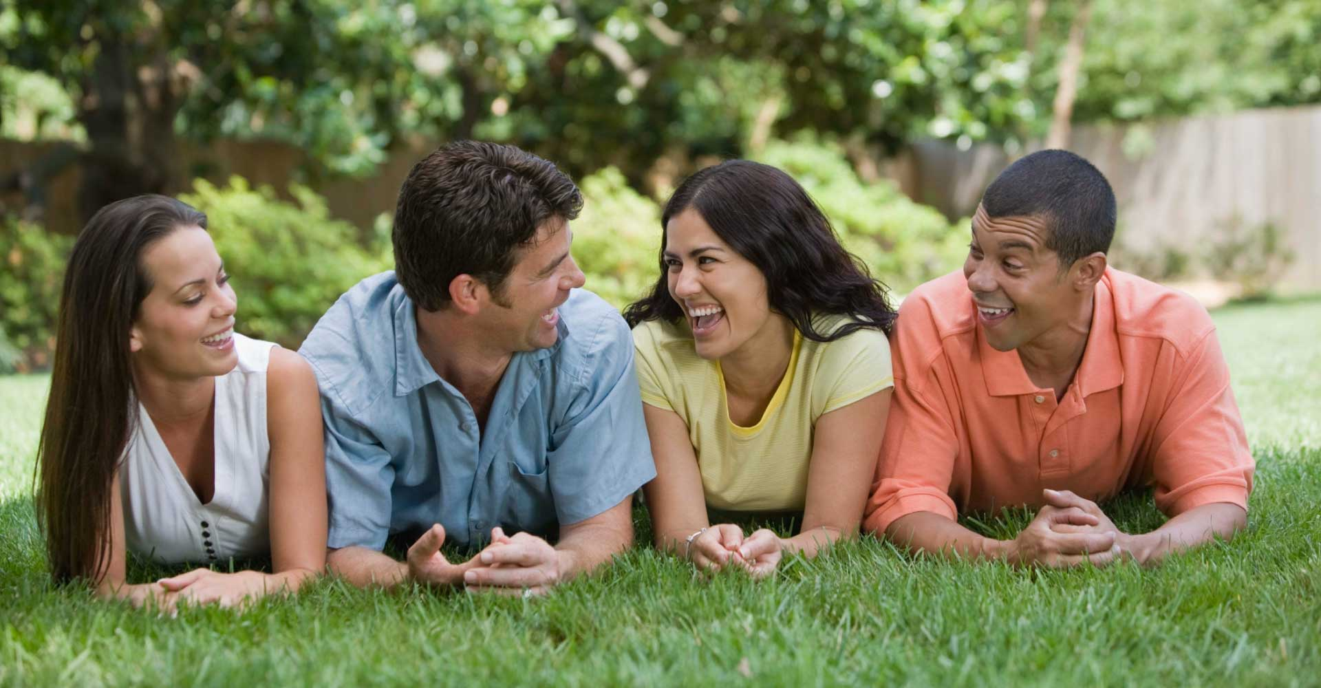 group of four smiling friends next to each other on their elbows in the grass