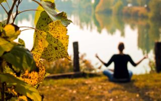 woman sitting in a meditation pose near a lake