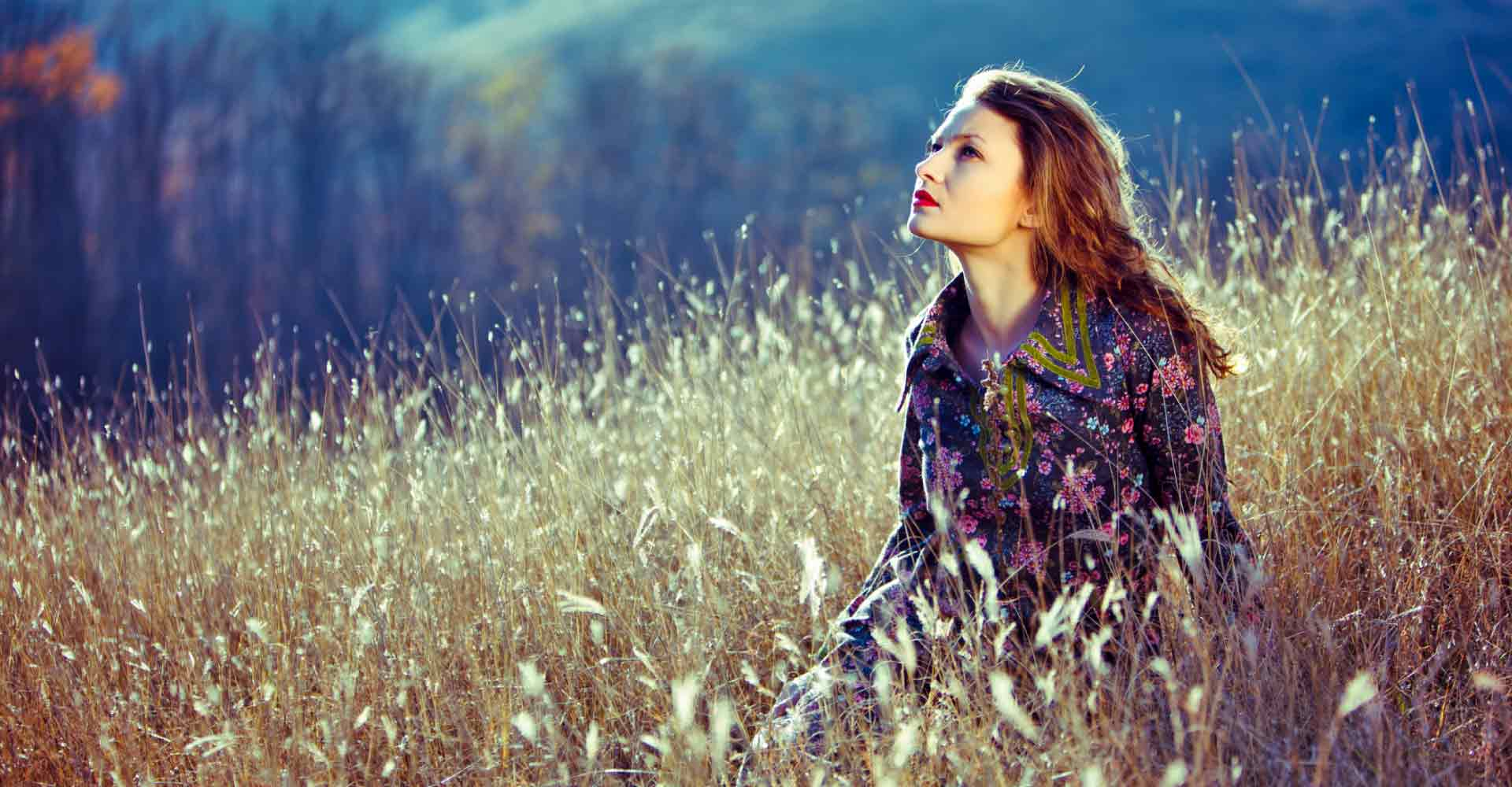 young woman in grassy field looking up and pondering life